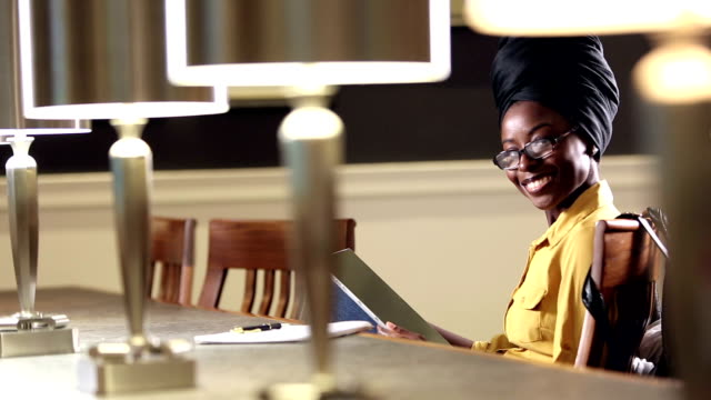 young african-american woman in library, digital tablet - headdress stock videos & royalty-free footage