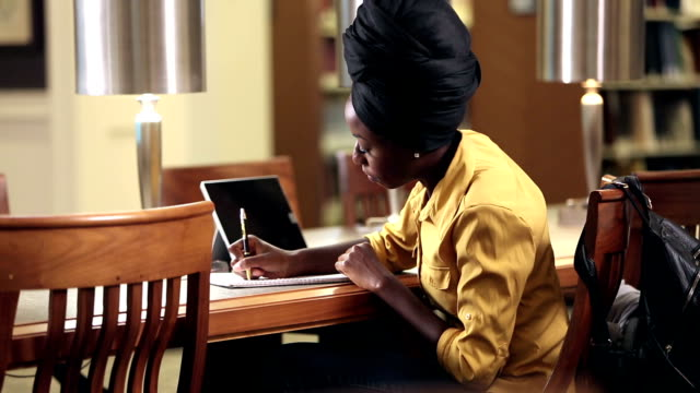 young african-american woman in library studying - headdress stock videos & royalty-free footage