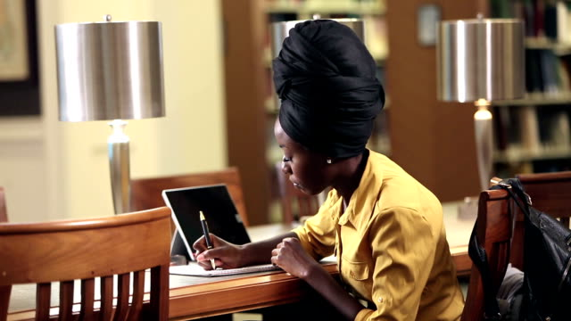 young african-american woman in library studying - headscarf stock videos & royalty-free footage