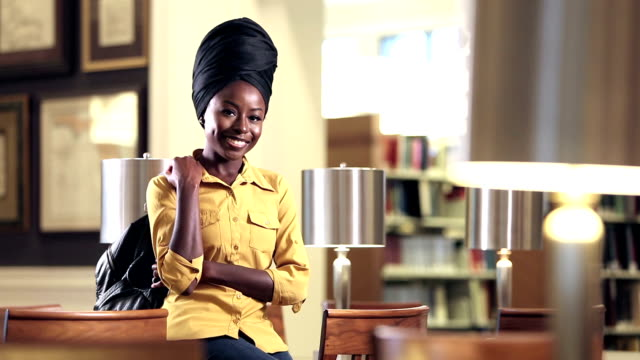 young african-american woman in library - headdress stock videos & royalty-free footage