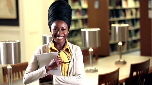 young african-american woman in library - turban stock videos & royalty-free footage