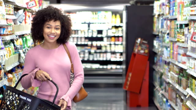 young african-american woman in supermarket aisle - shopping basket stock videos and b-roll footage