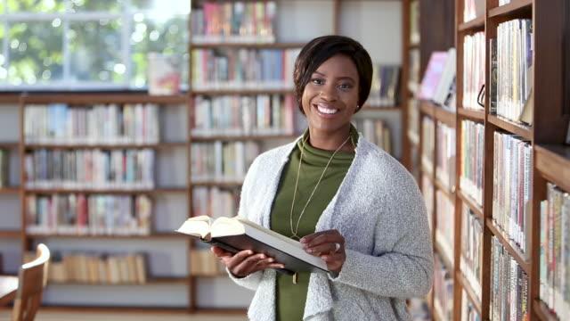 vídeos de stock e filmes b-roll de young african-american woman reading in library - professora