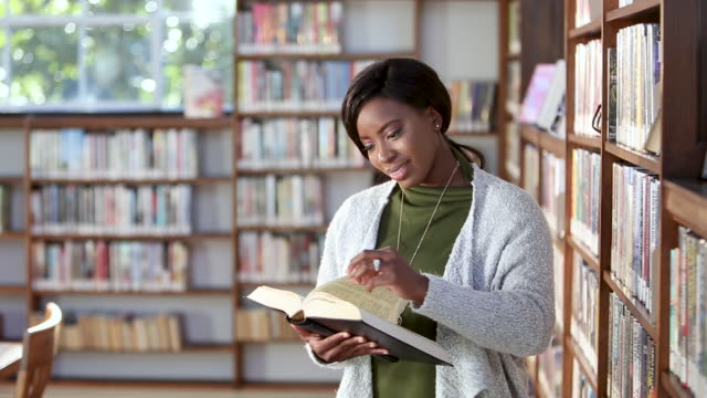 young african-american woman reading in library - librarian stock videos & royalty-free footage