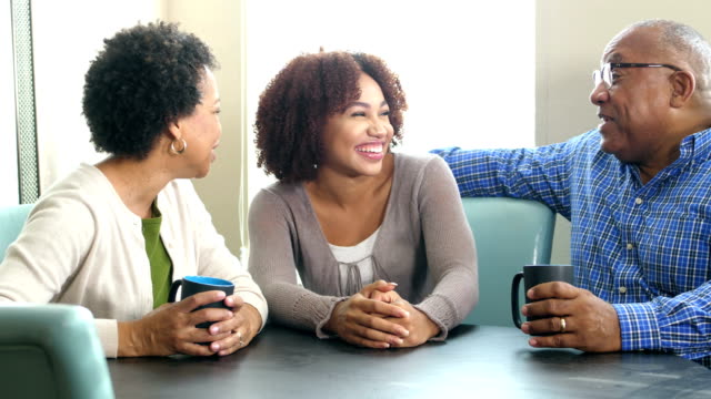 Young African-American woman talking with her parents
