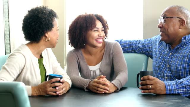 Jonge Afro-Amerikaanse vrouw praten met haar ouders