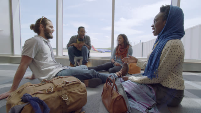 vidéos et rushes de young african-american woman talks and laughs with diverse friends while waiting at airport terminal gate. - salle d'embarquement