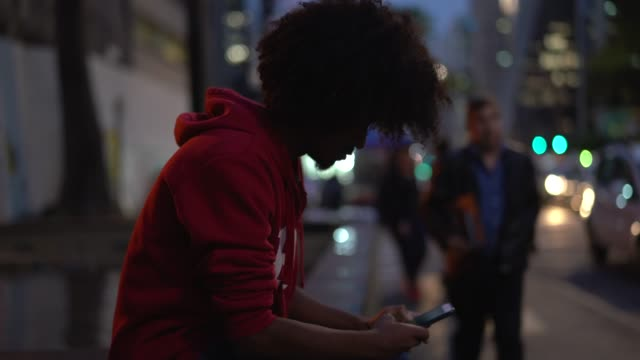 young afro man using mobile at avenida paulista, sao paulo, brazil - são paulo stock videos & royalty-free footage