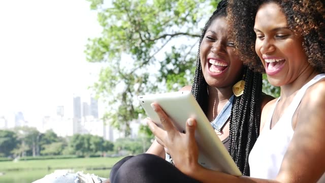 vidéos et rushes de jeune femme d'afro utilisant la tablette dans le parc - coiffure afro