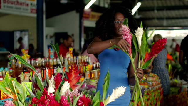 a young afro-caribbean market woman offers exotic flowers in a market hall in martinique - market stall stock videos & royalty-free footage