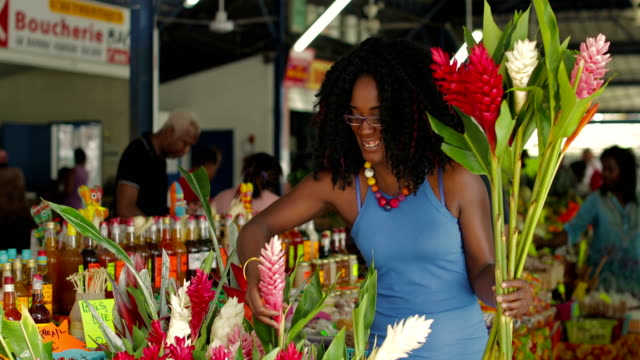 A young Afro-Caribbean market woman offers exotic flowers in a market hall in Martinique