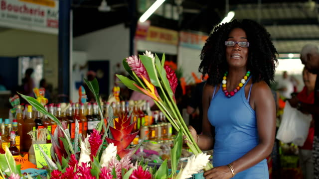 a young afro-caribbean market woman offers exotic flowers in a market hall in martinique - アフリカ系カリブ人点の映像素材/bロール