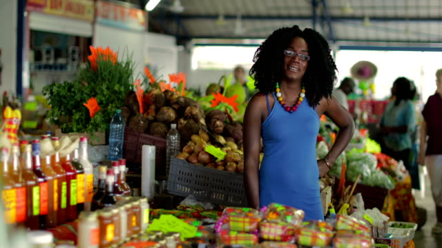 a young afro-caribbean market woman offers exotic flowers in a market hall in martinique - entwicklungsland stock-videos und b-roll-filmmaterial