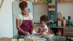 Young Afro-Caribbean Mother and Daughter Baking Together