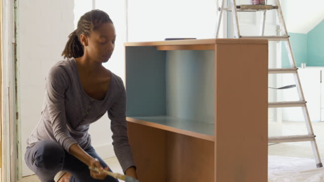 young afro-caribean woman renovating her home - cupboard stock videos & royalty-free footage