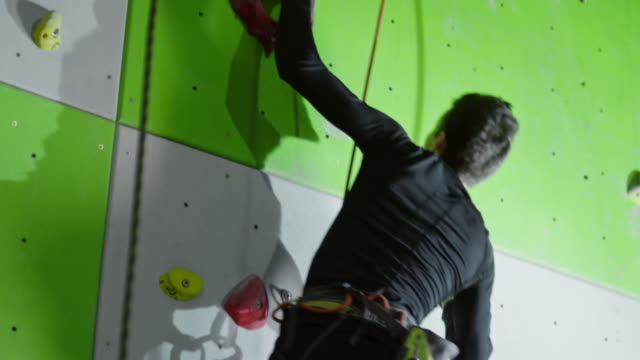 Young amputee athlete without leg going up on climbing wall