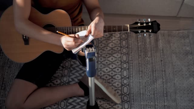 young amputee man playing guitar - songwriter stock videos & royalty-free footage