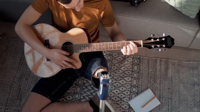 vídeos de stock e filmes b-roll de young amputee man playing guitar - confortável