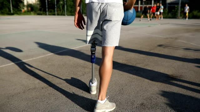 vidéos et rushes de jeune amputé avec un ballon de basket - personne sportive