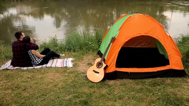 vídeos y material grabado en eventos de stock de pareja joven y hermosa sentada cerca del río en camping - tienda de campaña