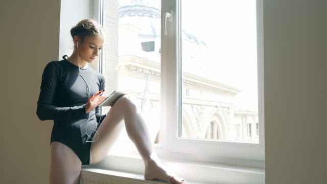 junge und schöne tänzerin mit digital-tablette mit kopfhörer. - nur junge frauen stock-videos und b-roll-filmmaterial