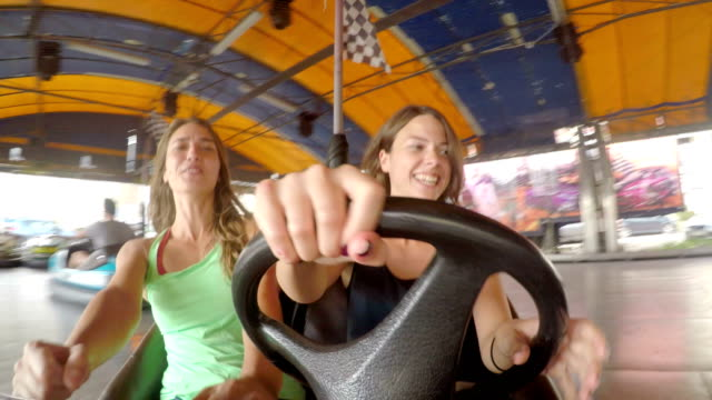 young and beautiful girls friends riding a electric car in amusement park - pulling funny faces stock videos & royalty-free footage