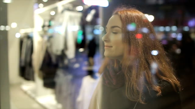 vídeos de stock e filmes b-roll de young and beautiful woman with red hair looking in the shop window - coleta seletiva