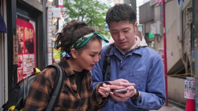 東京を探検する若くて気楽な中国人カップル - tourist点の映像素材/bロール