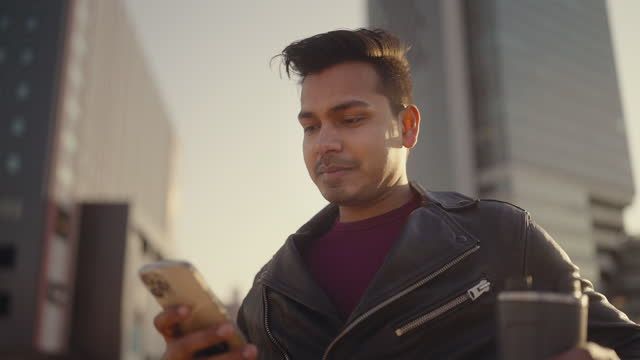 young and handsome indian man using smart phone in city - leather jacket stock videos & royalty-free footage