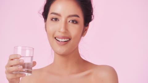 ピンクの背景に水を飲む若くて幸せな女性。清潔でバランスのとれた健康食品のコンセプト。健康的な食べ物、食事とフィットネスの概念.オーガニック食品。ヘルスケアと医療のコンセプト - ほっそりした点の映像素材/bロール