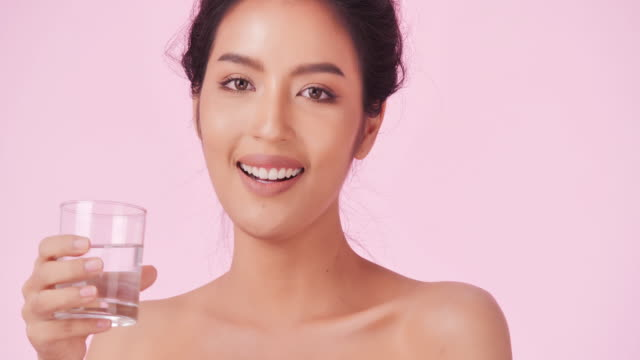 young and happy woman drinking water on pink background.clean and balanced healthy food concept.healthy food,diet and fitness concept.organic food.health care and medicine concept.video: diverse portraits - slim stock videos & royalty-free footage
