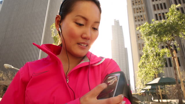 a young and healthy women checking her fitness device before running outdoors. - arm band stock videos & royalty-free footage
