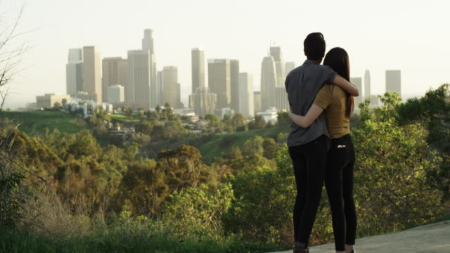 Young and hip lesbian couple hugging and watching the panorama of the city from above
