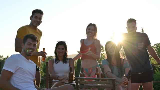 vídeos y material grabado en eventos de stock de amigos jóvenes y adultos medios disfrutando de la fiesta en la piscina por la tarde - voz