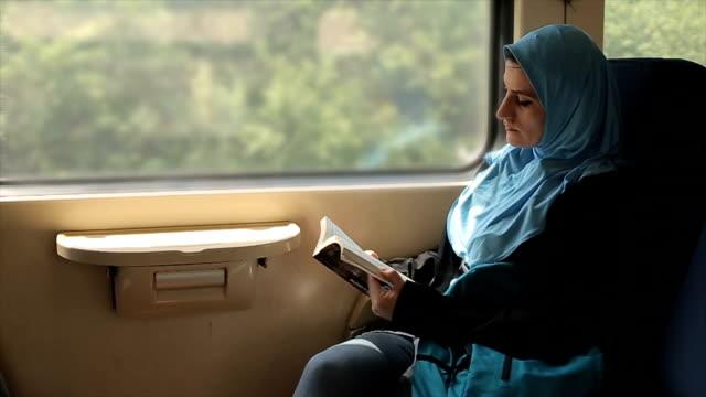 vídeos de stock, filmes e b-roll de jovem e mulher árabe moderna lendo livro no trem - vestuário modesto