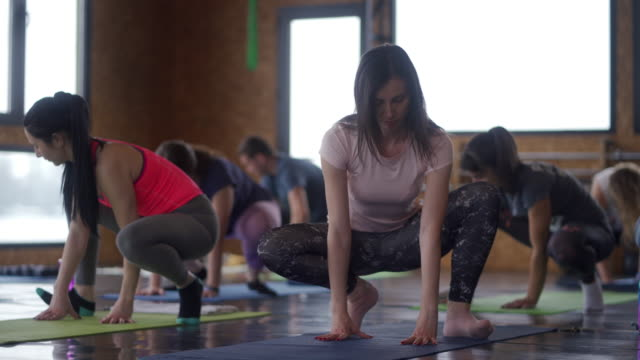 young and sporty people crouching and stretching their body on yoga mat - durevolezza video stock e b–roll