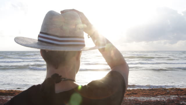 CU Young androgynous woman in straw hat looking out to sea.