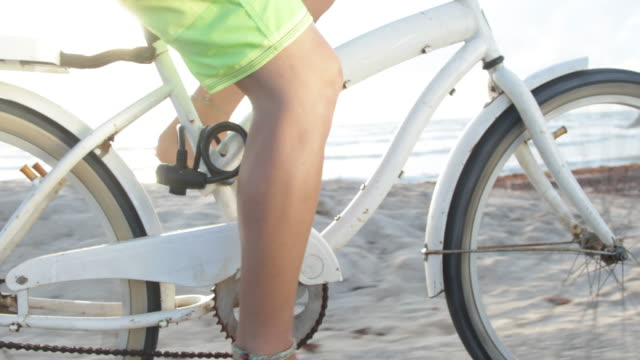 CU Young androgynous woman's legs on pedals, riding her bike.