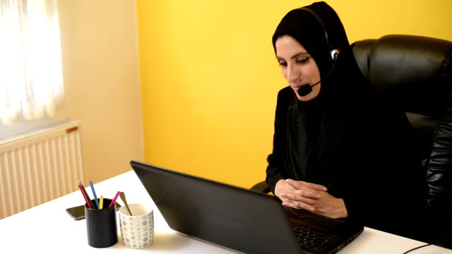 young arab businesswoman having a video conference with clients. - burka stock videos and b-roll footage