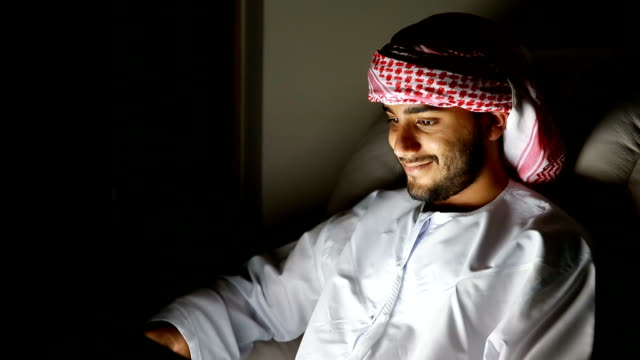 young arab using digital tablet in a dark room - e learning stock videos & royalty-free footage