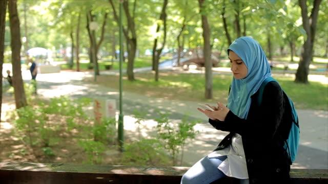 vídeos de stock, filmes e b-roll de mulher jovem árabe usando o telefone celular no parque - vestuário modesto