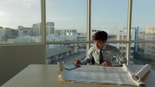 ms selective focus young architect looks over building plans on his desk / singapore - lageplan stock-videos und b-roll-filmmaterial