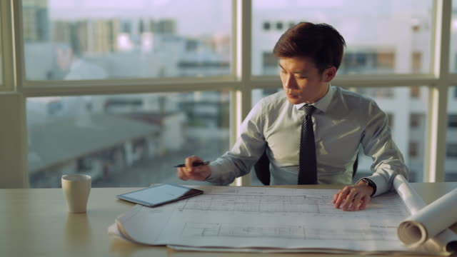 stockvideo's en b-roll-footage met ms selective focus young architect looks over building plans on his desk / singapore - overhemd en stropdas