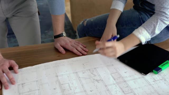 Junge Architekten auf Blaupausen in casual Büro arbeiten und sprechen über neue Business-Pläne.