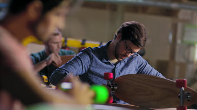 Young artisans assemble longboard kits in modern wood shop