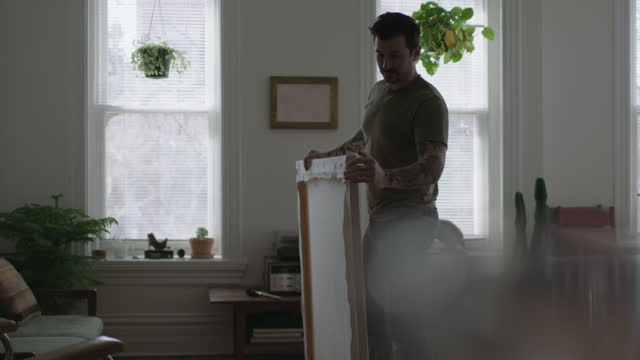 WS SLO MO. Young artist brushes off and inspects blank canvas in sunny city apartment.