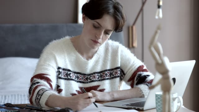 young artist drawing while looking at laptop in apartment - young women video stock e b–roll