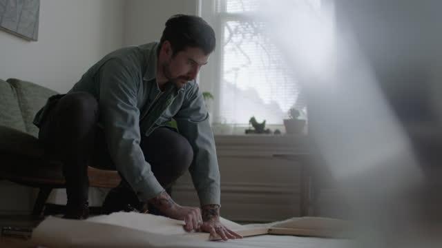 vidéos et rushes de slo mo. young artist fold canvas over wooden frame on apartment floor. - toile à peindre