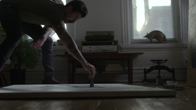 ws slo mo. young artist leans over canvas and paints in broad strokes on apartment floor. - pennello video stock e b–roll