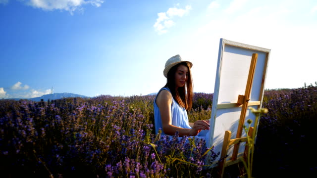 young artist painting an floral landscape - pittore video stock e b–roll